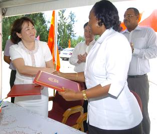 Mrs Tang (left) and Mrs Azemia exchanging the signed documents. On the right is Speaker Herminie. Centre is Ambassador Wenbing