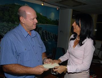 Mr St Ange accepting the contribution of Coral Strand, whose representative was the only one present at the hand over ceremony