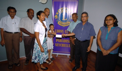 Mrs Bonte accepts the cheque from Lions president N. Ramani