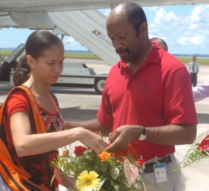 Minister Meriton hands over the basket of flowers to singles gold medallist Ah-Wan