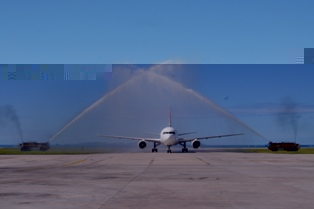 The plane is welcomed by a traditional water cannon spray mounted by the airport fire services