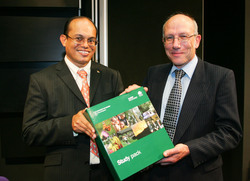 Dr Payet, left, is presented with one of the distance learning module study packs by Professor Dorward