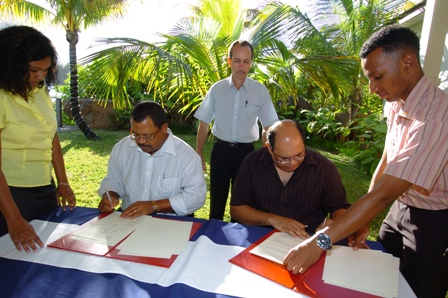 Mr Payet (right) and Mr Toussaint signing the documents to officially set up the fund