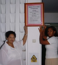 Mrs Orr (left)  placing a framed copy of the ministry's vision statement in the lobby of Unity House
