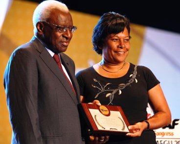 Ms Rousseau receiving the IAAF Plaque of Merit from IAAF president Lamine Diack