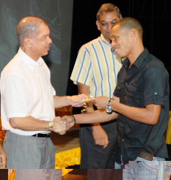 President Michel presents footballer Jones Joubert, on behalf of the team, with their monetary rewards for the gold medal won on a penalty shootout against Mauritius