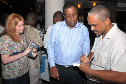 The author autographing copies of the book that guests had bought at the launch