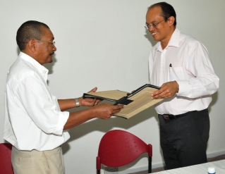 Dr Payet and Mr Racombo exchange documents after the signing