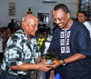 Minister Sinon presenting token to 10-year awardee, James Malvina.