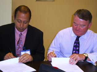 Messrs Simeon (left ) and Gray initialing the agreement