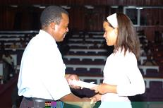 A graduate receives her certificate from Mr Port-Louis