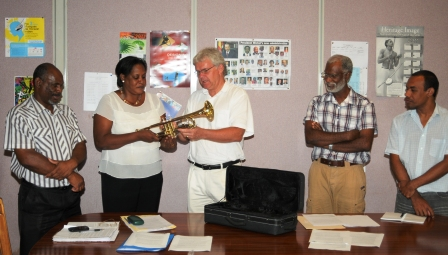 Mrs Onezime accepts the trumpets from Mr Swenson in the presence of staff from the department of culture and the school of music