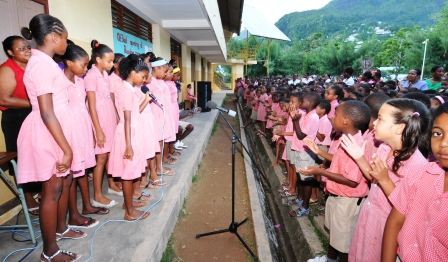 The children applaud as the school's choir sings