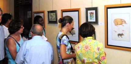 Des visiteurs admirant la qualité du travail exposé par M. Gerlach à l'Alliance Française