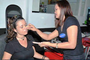Essence's make-up artist Mary-Jane Cambel (right) applying foundation to Betty Reverra's face