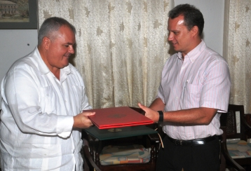 Minister Adam and Mr Luz exchange documents after signing the agreement