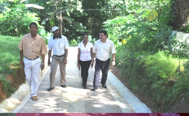 The delegation walking along a newly built feeder road at Anse Louis
