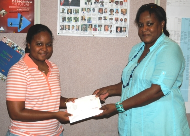 Ms Ernesta receiving her travel documents from Ms Onezime