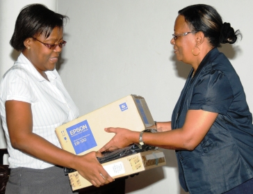 Mrs Simeon (right) hands over the donation of laptops and projectors to a representative of the department