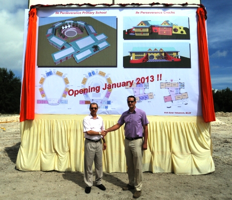 President Michel and PS Lionnet shake hands after unveiling the project banner for the new school