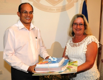 Dr Payet accepting the books from Dr Budgen