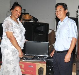 Ms Valmont accepting the computer sets from Ambassador Shi