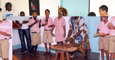 Achille 'Kwame' Luc, accompanied by a group of Au Cap pupils, performing a musical piece
