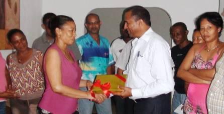 Black River district council president Krishna Rutnee handing a copy of the books to head teacher Milena Richard