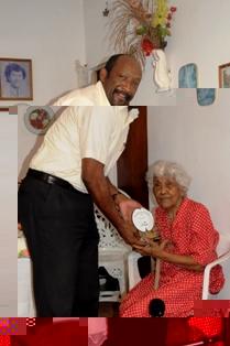 Mrs Vital accepts the commemorative senior citizens' shield from Mr Meriton