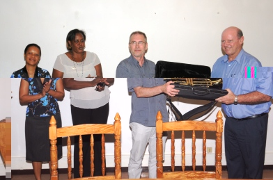 Mr St Ange (right) accepting the donation of trumpets from Mr From