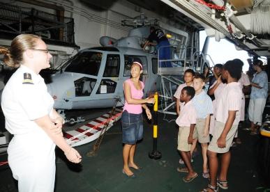 Les enfants admirant l'hélicoptère dans le hangar de la frégate