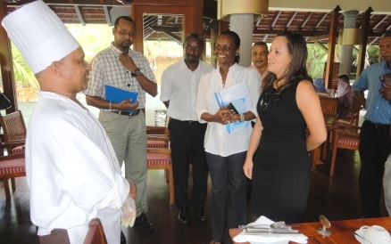 A Sainte Resort & Spa worker talking to Minister Alexander and members of her delegation