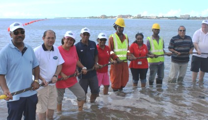Minister Sinon leads the way by pulling the fibre optic cable ashore on Msasani beach accompanied by SCS's representatives and partners in the project
