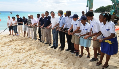 President Michel and other dignitaries, company representatives and school children symbolically pulling the cable towards the shore near Beau Vallon's La Plage restaurant