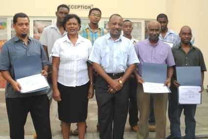 The certificate recipients in a souvenir photograph with Minister Sinon and Mrs Quatre