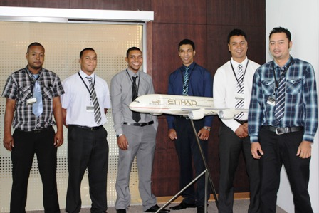 The Seychellois technicians posing at the Ethihad Airways headquarters in Abu Dhabi alongside a model of an Airbus A380, the world's largest passengers aircraft