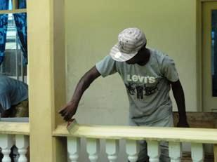 A member of the Les Mamelles team giving a fresh coat of paint to one of the hospital's room verandas