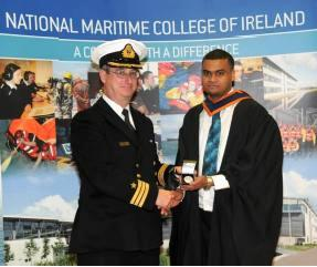Martin Roucou receiving the award of best marine engineering graduate of the year from Commander Michael Malone
