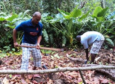 Two members of the Outsiders team preparing land for tree planting