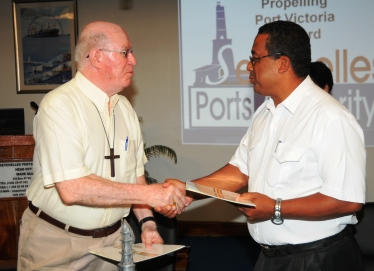 Bishop Wiehe and Lt Col Ciseau exchanging documents after signing the MoU
