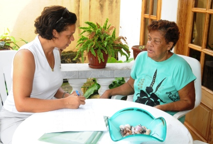 A survey team member collecting information from Ms Vanessa Emilie at her Forêt Noire home Wednesday as part of a study that will help set future minimum wages