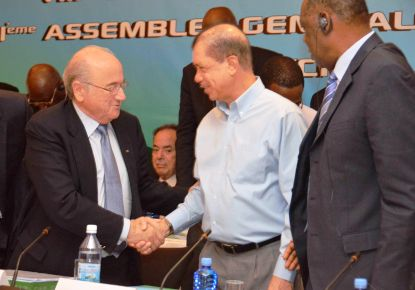 President Michel shakes hands with Fifa president Blatter as Caf boss Hayatou looks on