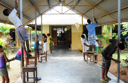 Plaisance secondary students cleaning the metal beams before giving the district's crèche a fresh coat of pain