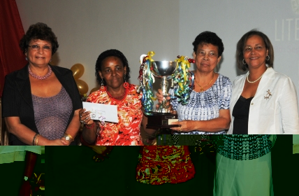 Representatives of the best overall district displaying their prizes in a souvenir photograph with Minister Mondon (left) and one of the sponsors Jeanine Chung-Faye (right)