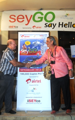 Minister St Ange and Mr Pool shake hands after unveiling the banner to officially launch the SeyGO visitor pack