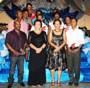 Those who received awards in a souvenir photograph with Minister Mondon and her principal secretary Merida Delcy