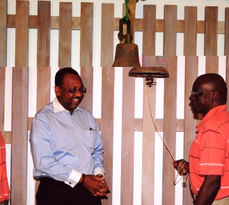 Minister Sinon looks on as Mr Belmont rings the bell to mark the launch of the Tonbola Lagrikiltir