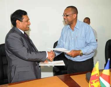 Dr Senaratne (left) and Minister Sinon exchange documents after signing the MoU