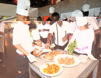 A group of disabled children try their hands at pizza making during a fun day hosted by the Le Meridien Barbarons hotel on Monday.