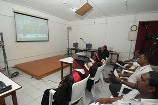 Guests and graduates watching the ceremony on the screen